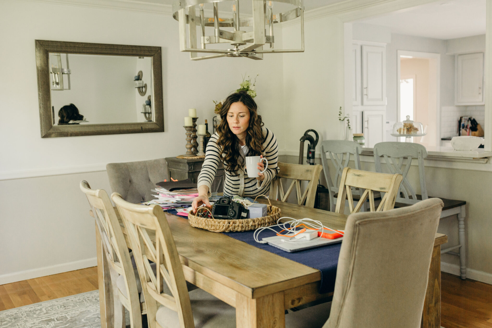 Mom holding cup of coffee arranging messy dining room table
