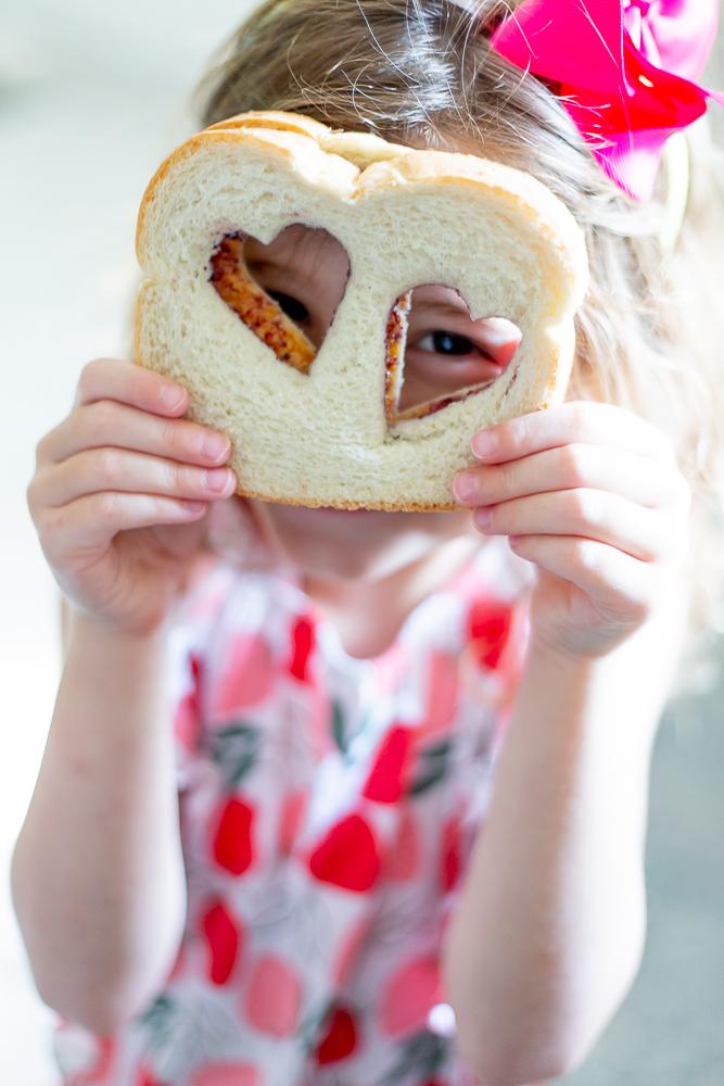 little girl peeking through sandwich for school