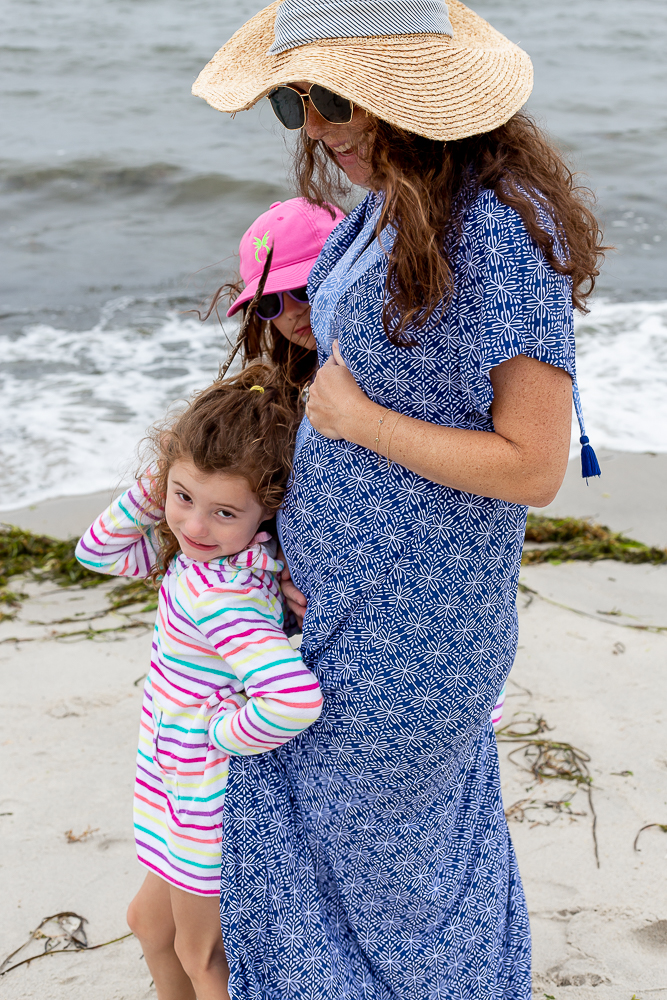 24 weeks pregnant mom at beach August 2021 with two older daughters