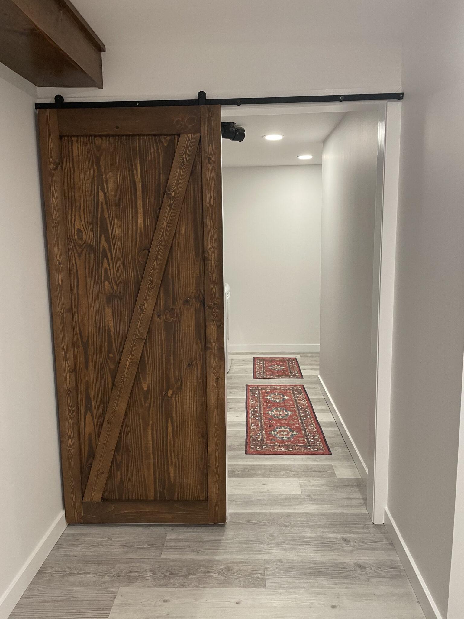 dark wood barn door gray floors laundry room